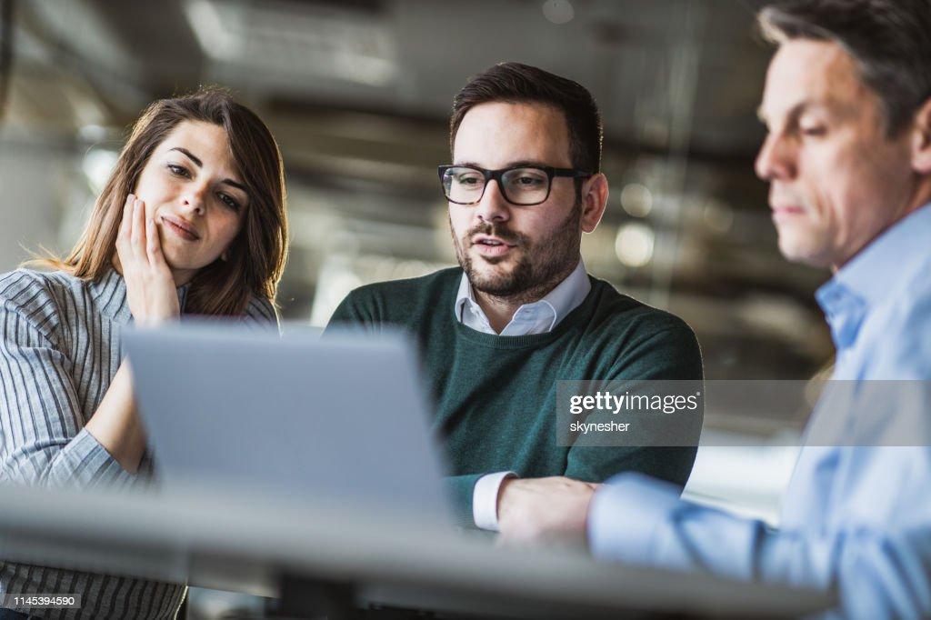 Jong koppel en makelaar met behulp van laptop op een vergadering in het kantoor. : Stockfoto