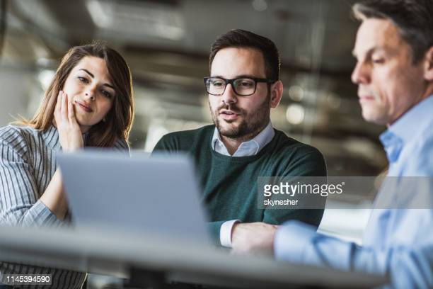 young couple and real estate agent using laptop on a meeting in the office. - mortgage stock pictures, royalty-free photos & images