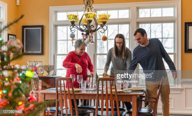 young couple and senior woman, a mother, laying the table for the christmas holiday family dinner. - judaism stock pictures, royalty-free photos & images