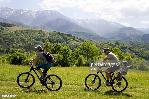 young couple and their child on a mountain bike trip - eco tourism stock pictures, royalty-free photos & images
