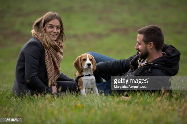 young couple and their cute puppy in a green park - vaud canton stock pictures, royalty-free photos & images