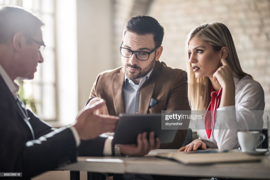 Young couple and their real estate agent looking at housing plan on touchpad in the office. : Stock Photo