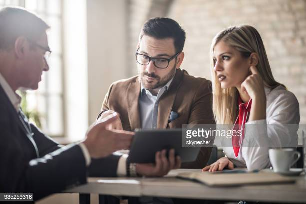 young couple and their real estate agent looking at housing plan on touchpad in the office. - finanza foto e immagini stock