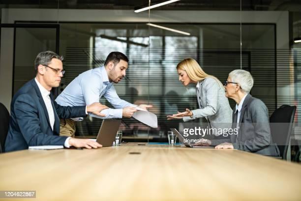 jeunes couples se disputant au sujet de la paperasserie sur une réunion avec leurs avocats. - conflit photos et images de collection