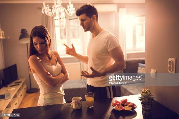 young couple arguing at home. - scolding stock pictures, royalty-free photos & images