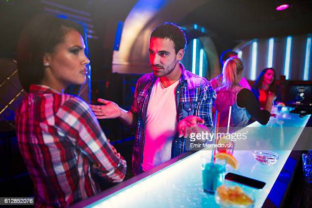 Young couple arguing in a nightclub