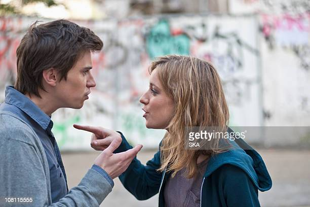 young couple arguing in street - couple arguing stock photos and pictures