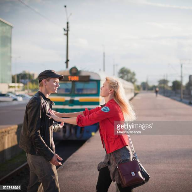 Young couple arguing on platform after missing train