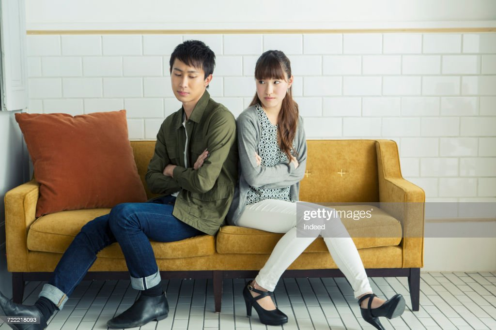 Young couple arguing on sofa : Stock Photo