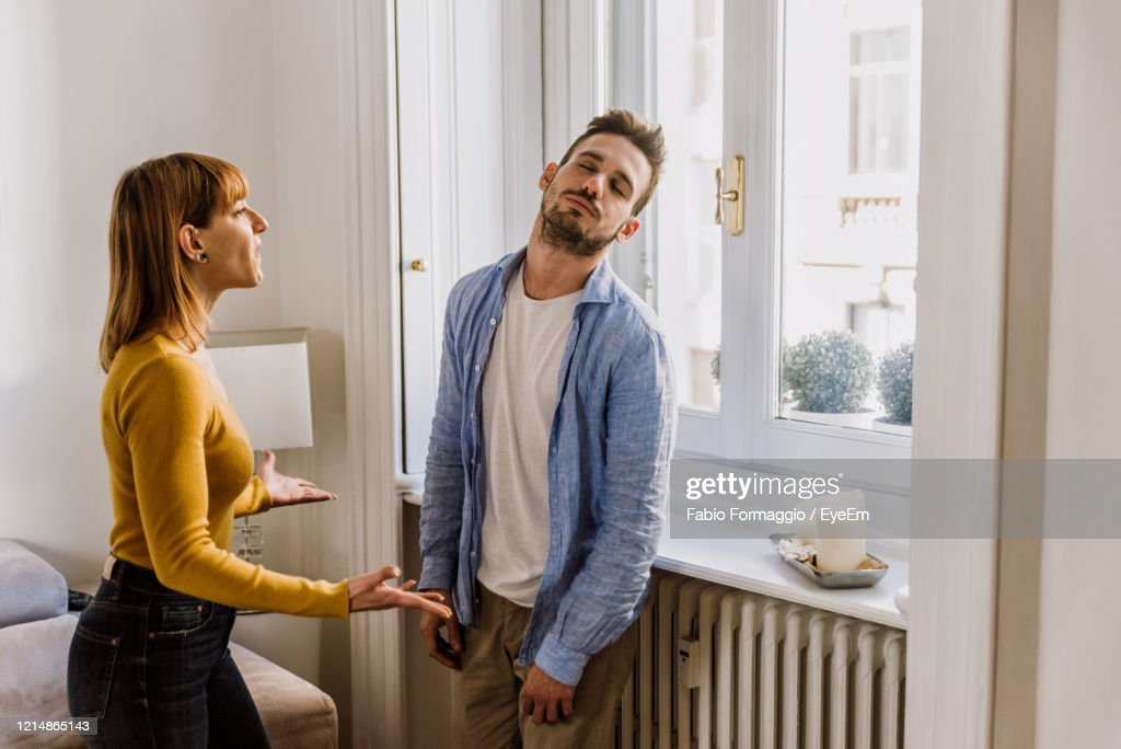 Young Couple Arguing While Standing At Home : Stockfoto