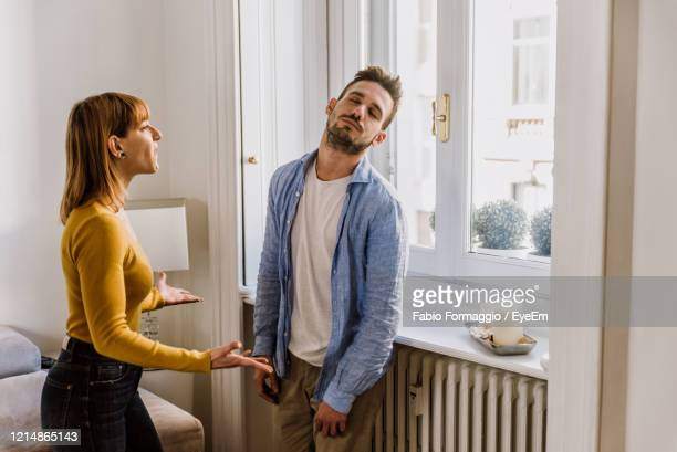 young couple arguing while standing at home - conflict stockfoto's en -beelden