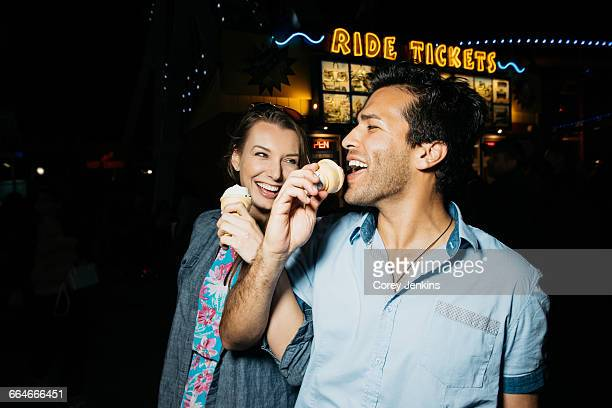 young couple arm in arm eating ice cream in amusement park at night, santa monica, california, usa - arm in arm stock pictures, royalty-free photos & images