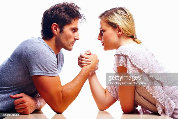 young couple arm wrestling against white background - women dominating men stock photos and pictures