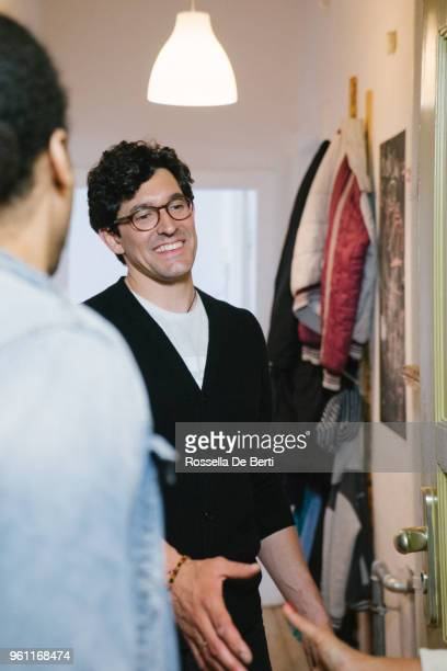 young couple arriving at holiday apartment - welcoming guests stock photos and pictures