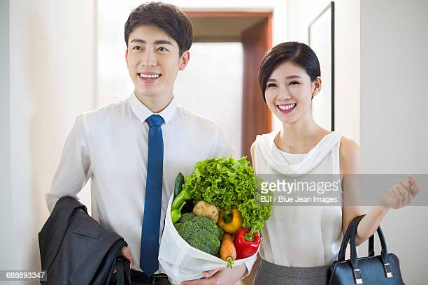 Young couple arriving home with fresh vegetables