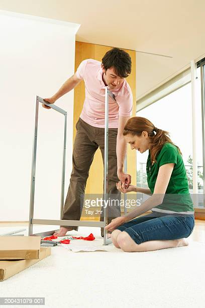 Young couple assembling flat-pack furniture, low angle view