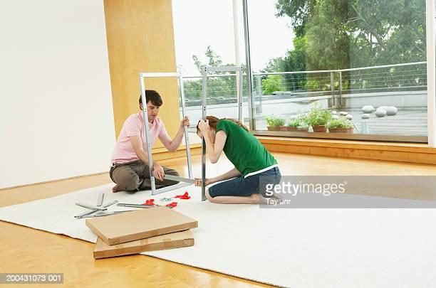 Pareja joven formación CON PANTALLA PLANA-PAQUETE muebles, vista a través de la habitación