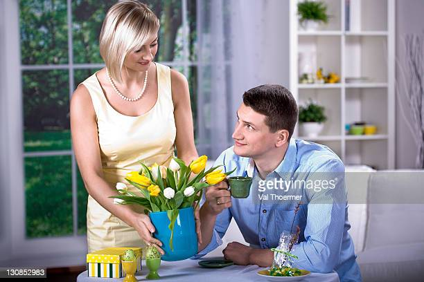 young couple at a table with tulips in a vase and easter eggs - happy resurrection day stock pictures, royalty-free photos & images