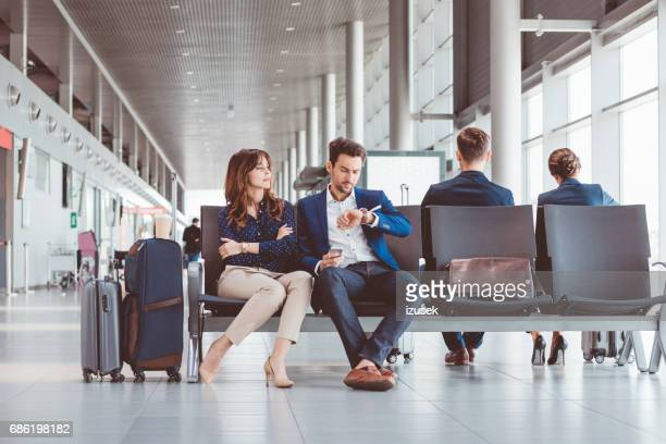 Young couple at airport lounge waiting for their flight