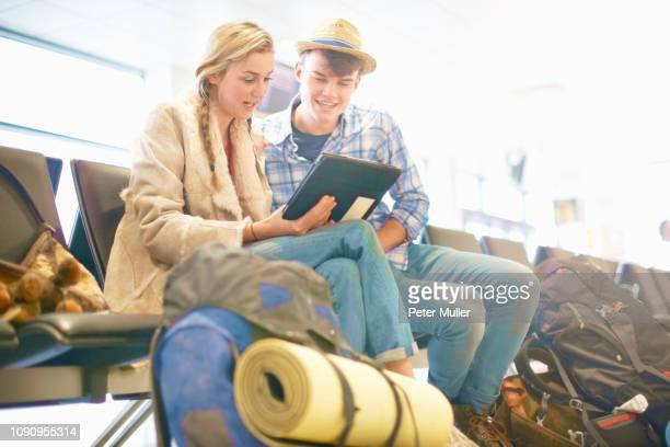 young couple at airport, sitting, surrounded by backpacks, using digital tablet, low angle view - 日常から抜け出す ストックフォトと画像