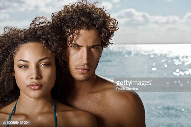 Young couple at beach, portrait, close-up