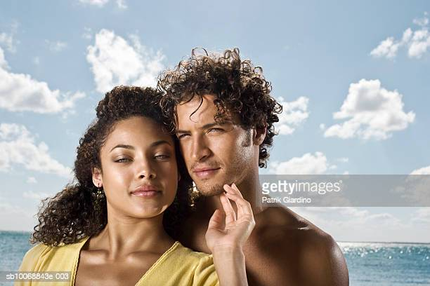Young couple at beach, portrait, smiling, close-up