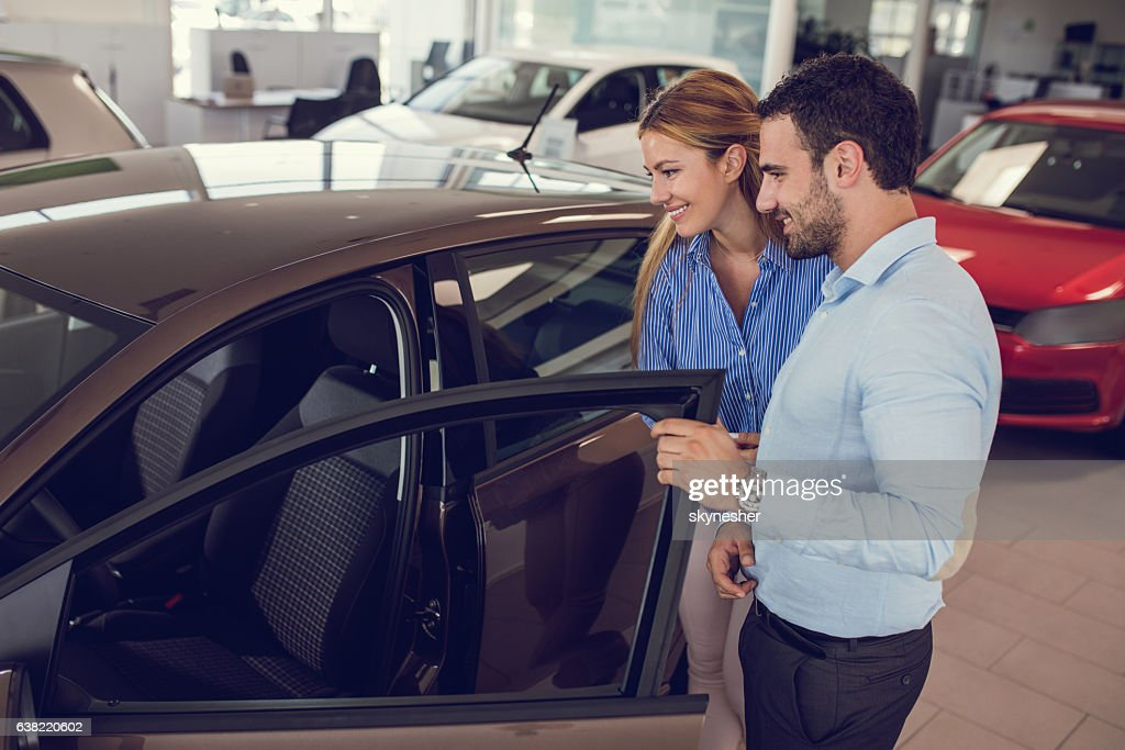 Young couple at car dealership looking at new car together. : Stock Photo