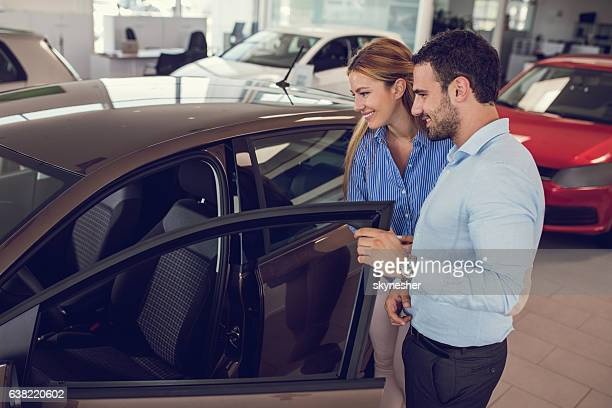 Young couple at car dealership looking at new car together.