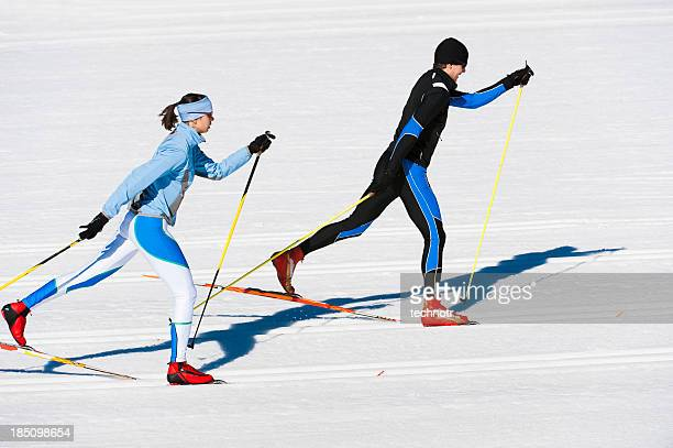 young couple at cross country skiing - langlaufen stockfoto's en -beelden
