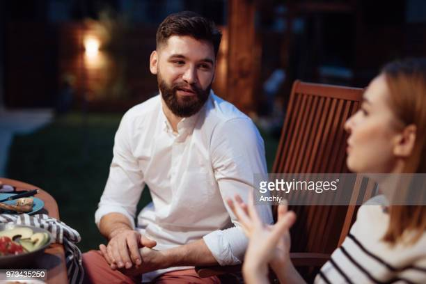 Young couple at dinner party, talking and drinking wine