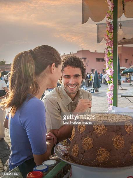Young couple at food stall in market, Jemaa el-Fnaa Square, Marrakesh, Morocco