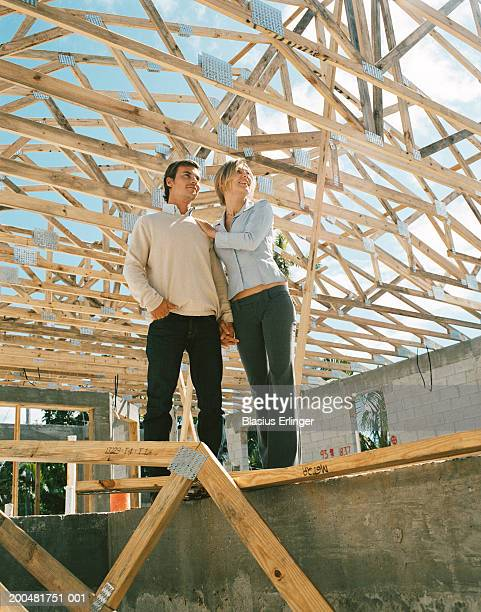 young couple at home construction site looking upwards - blasius erlinger stock pictures, royalty-free photos & images