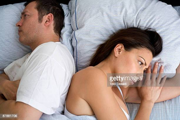 young couple at home in bed - couple fighting stockfoto's en -beelden
