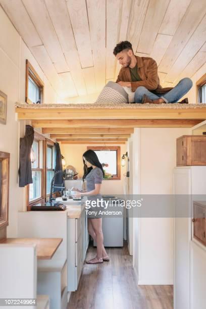 young couple at home in their tiny house - wohngebäude innenansicht stock-fotos und bilder