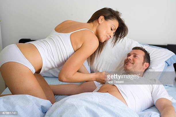 young couple at home relaxing in bed - sensuality stock pictures, royalty-free photos & images