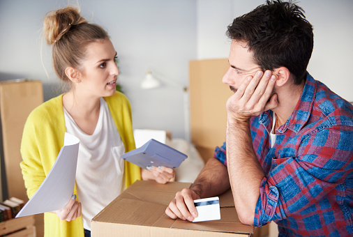 Young couple at home, surrounded by cardboard boxes, working out finances - gettyimageskorea