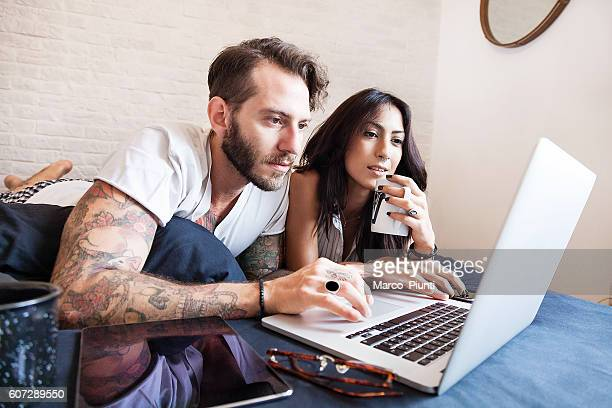 Young couple at home - Using computer on the bed