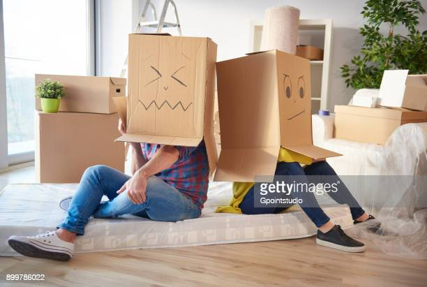 young couple at home, wearing cardboard boxes on heads, faces drawn on boxes - demenagement humour photos et images de collection