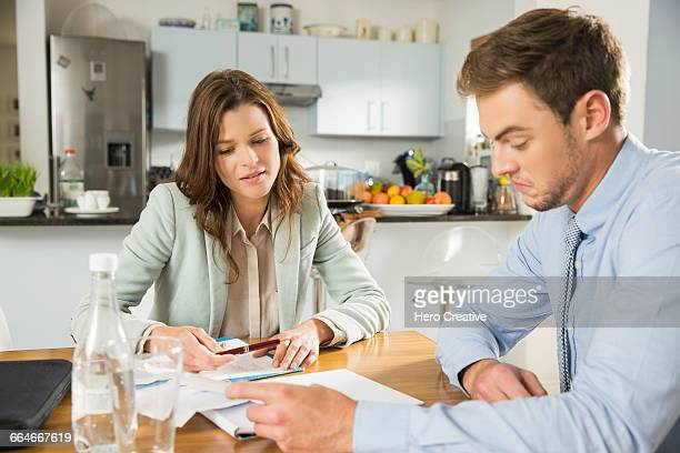Young couple at kitchen table reading bills and paperwork