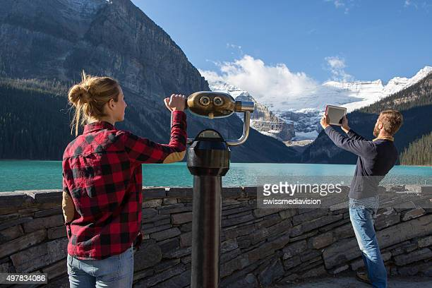 Young couple at lake Louise looking at glacier from viewfinder