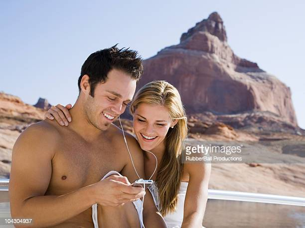 young couple at lake powell listening to music on an mp3 player
