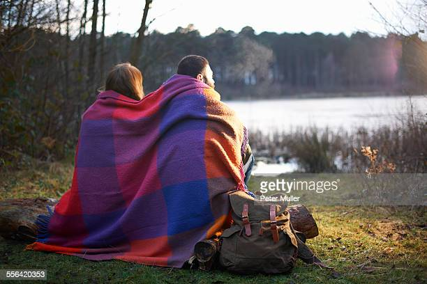 Young couple at lakeside wrapped in blanket at sunset