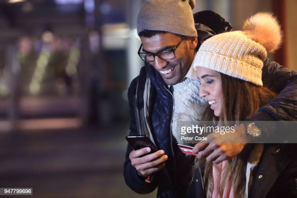 Young couple at night, paying for something on phone with card