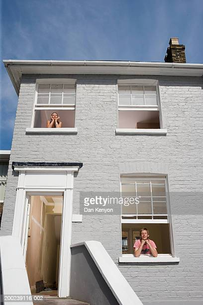 Young couple at seperate windows, both resting chin on hands