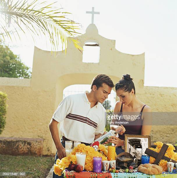 young couple at shrine in front of church gate - day of the dead stock photos and pictures