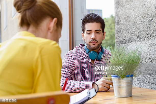 Young couple at sidewalk cafe table