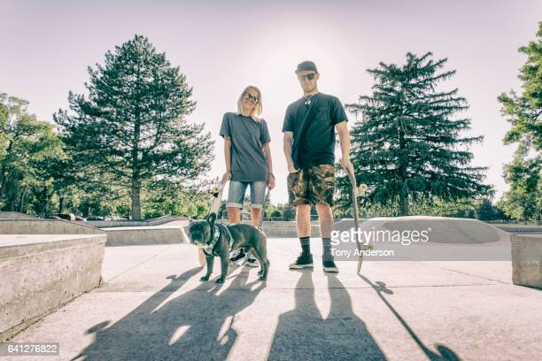 young couple at skatepark with their dog - things that go together stock pictures, royalty-free photos & images