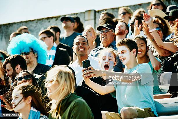 young couple at soccer match taking selfie - sports event stock pictures, royalty-free photos & images