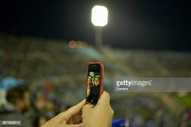 Young couple at soccer match taking selfie Portrait