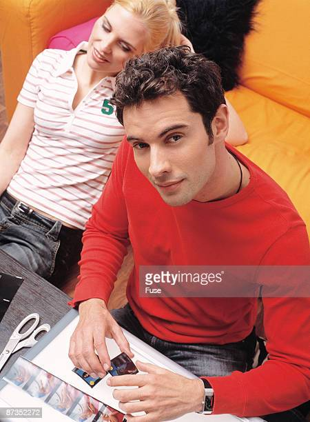 Young couple at sofa, man looking to slides under ligthbox